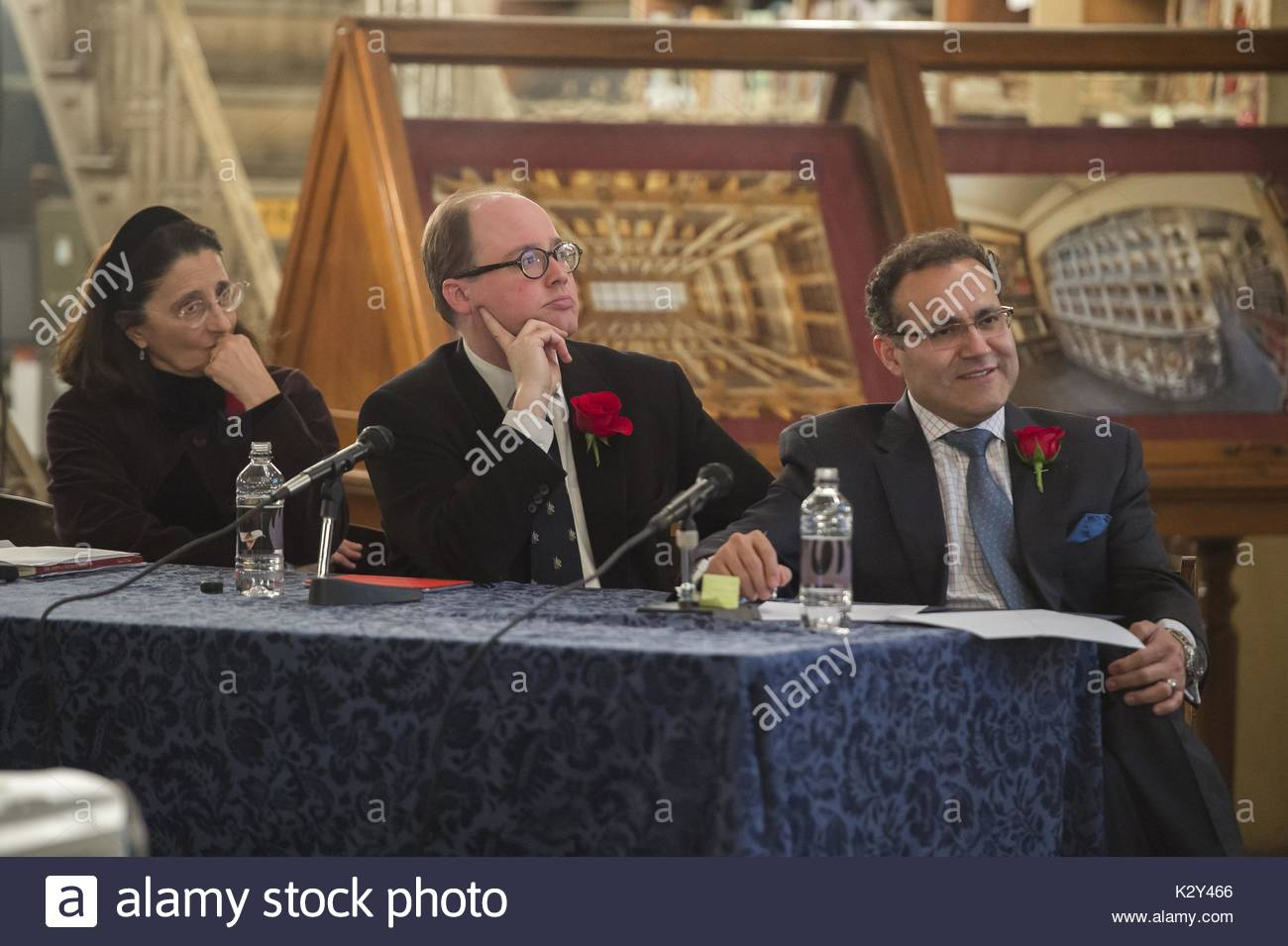 Three formally dressed panelists seated at a table with microphones look intently at a speaker at a panel on the brain at the Johns Hopkins University's George Peabody Library, Baltimore, Maryland, 2014. - Stock Image