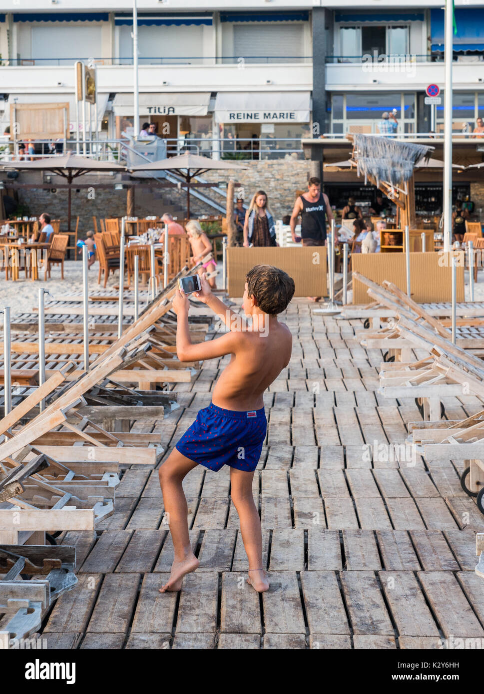 A young boy takes a silly selfie on a pier in Juan les Pins, France - Stock Image