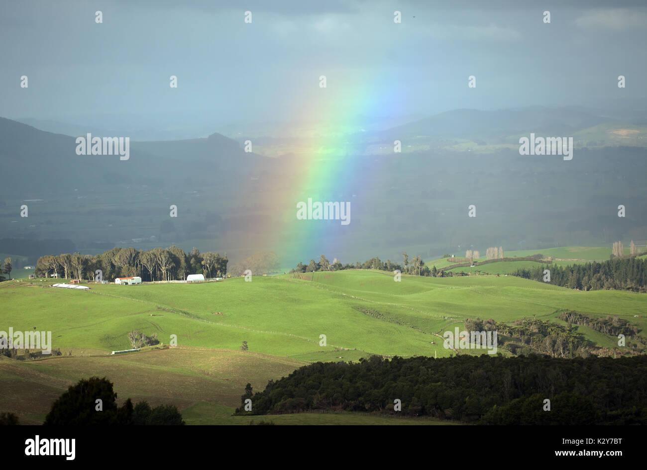 Rainbow close-up  looking towards the flank of Kakepuku Volcano from Te Awamutu, North Island, New Zealand - Stock Image