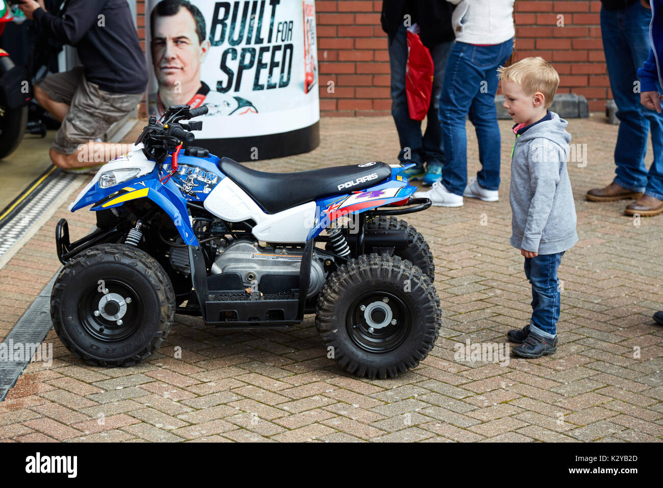 Small boy looks on at John McGuinness' mini quad bike at the Manx Classic TT races, Isle of Man - Stock Image