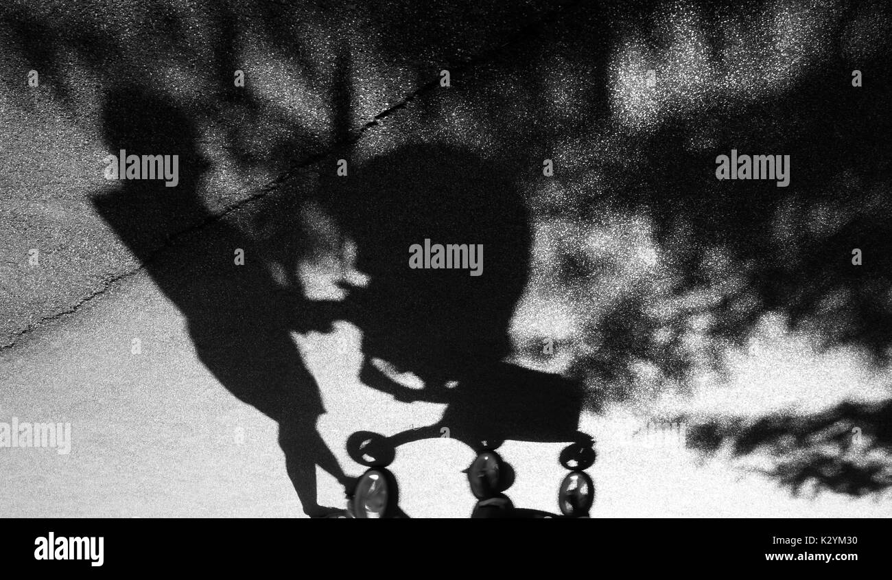 Blurry shadow of a woman with postpartum depression pushing a baby trolley on the cracked asphalt suburban park road in black and white - Stock Image