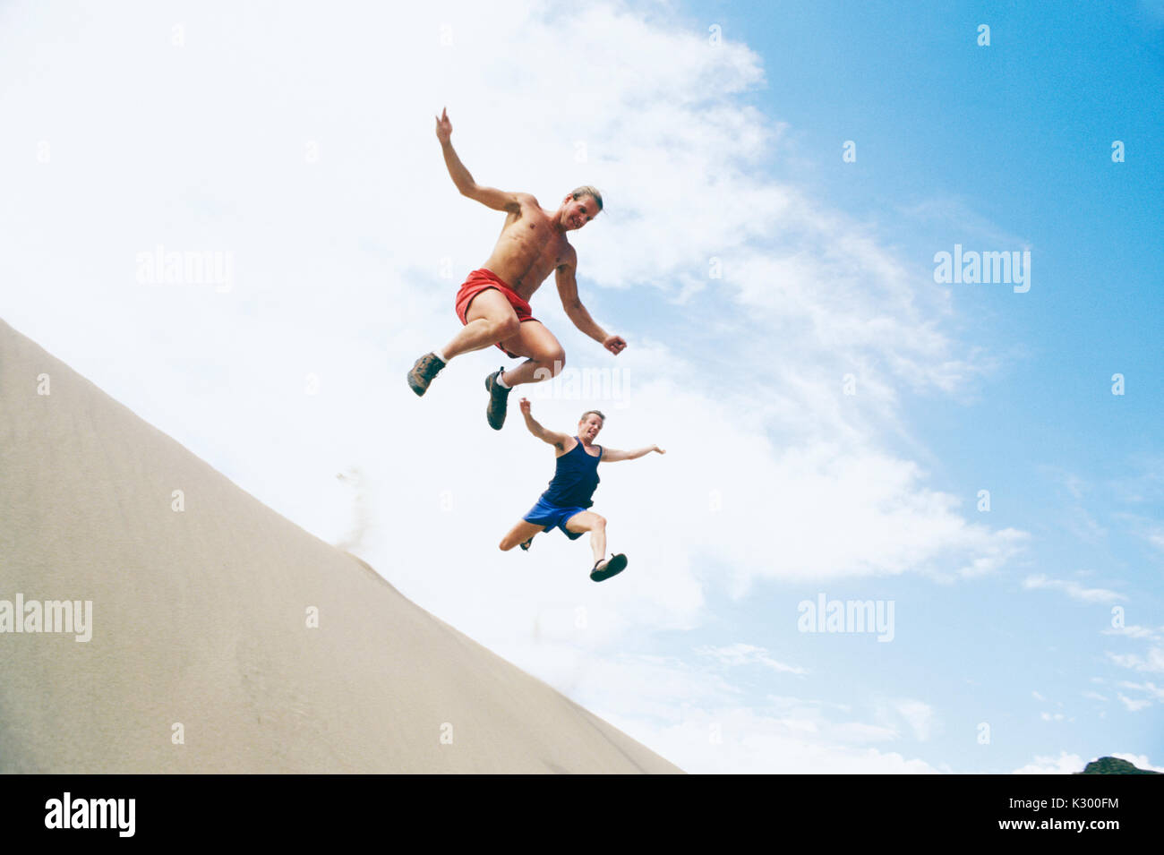 Two late 20's Caucasian men leaping off a sand dune.  Near Vantage, Washington, USA.  Frenchmans Coulee. - Stock Image