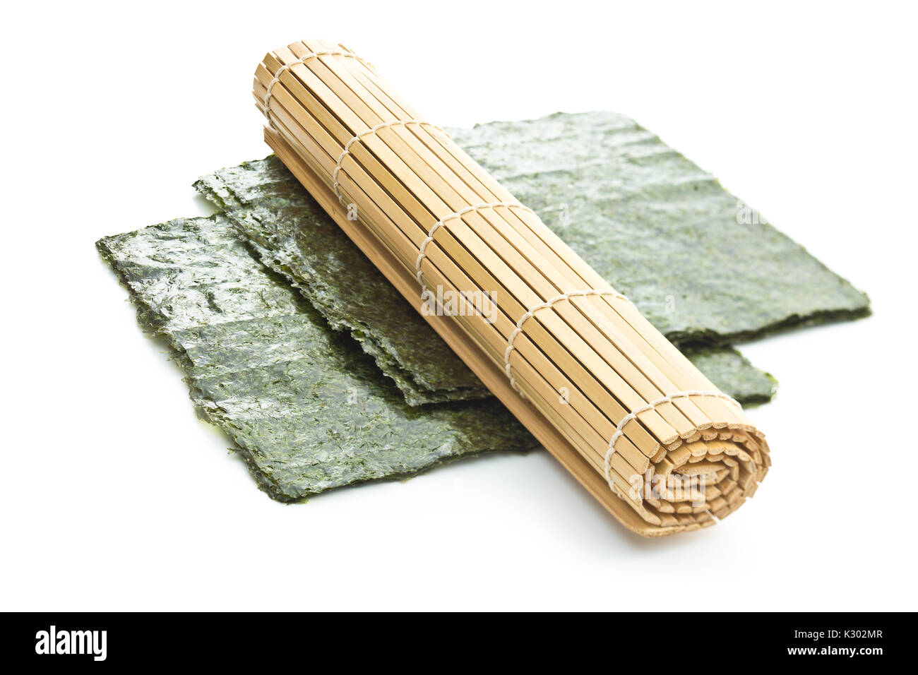 Green nori sheet and bamboo mat isolated on white background. - Stock Image