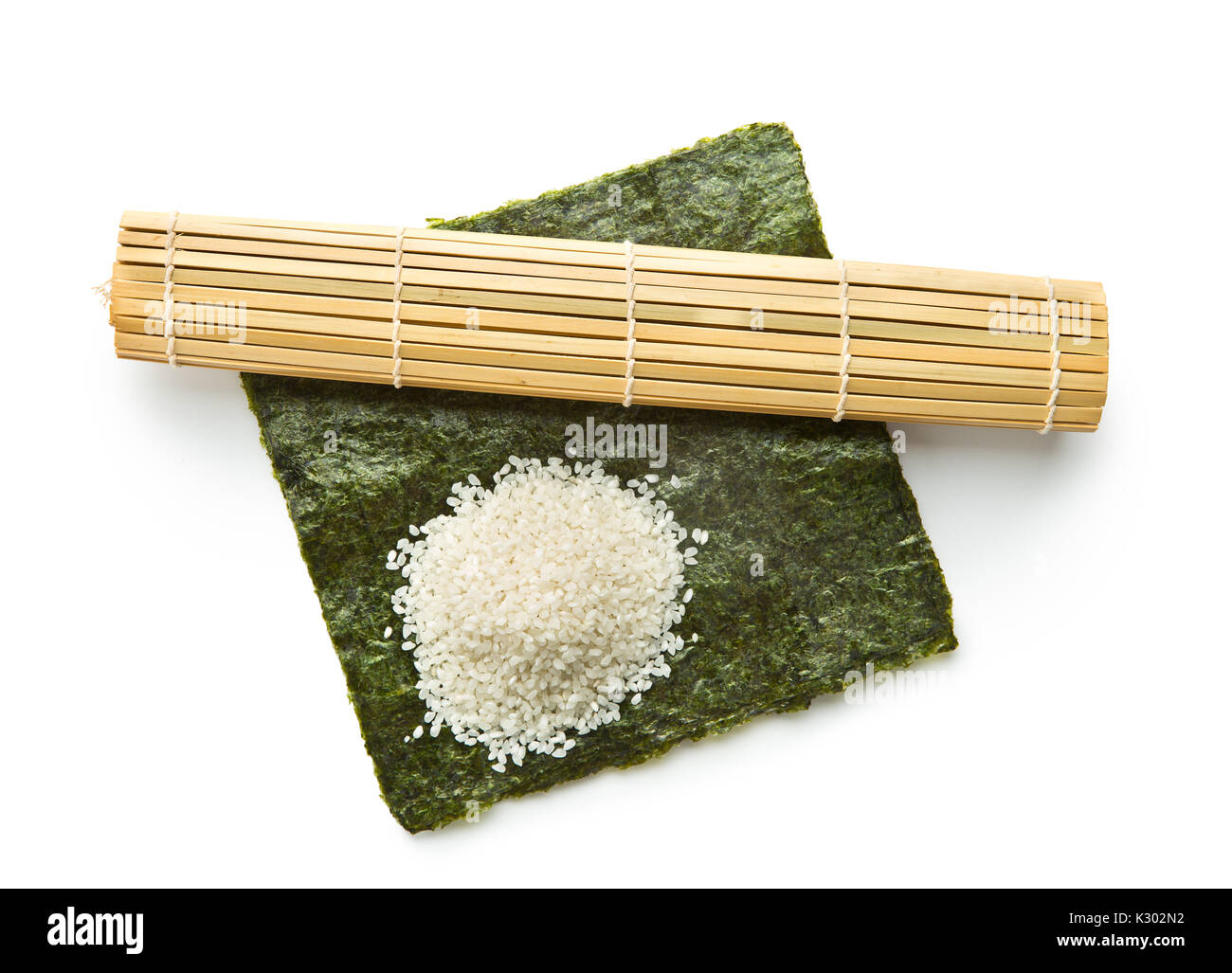 Green nori sheet , rice and bamboo mat isolated on white background. Sushi ingredients. - Stock Image