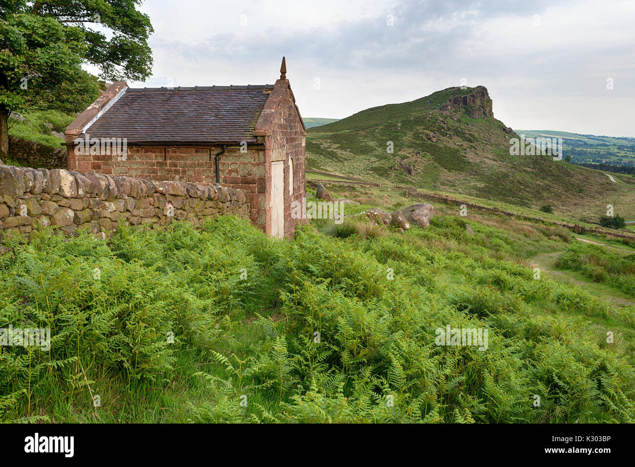 An old stone hut on the edge of The Roaches in the Peak District National Park in Staffodshire, looking out at the peak of Hen Cloud - Stock Image