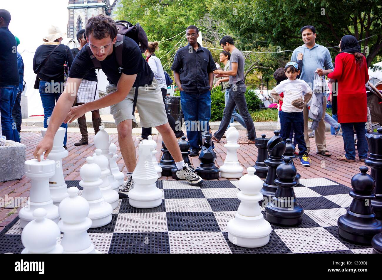 A man wearing a backpack reaches to move the king piece from a life-sized chess set, while onlookers behind him observe his strategy, during Baltimore Book Festival, Baltimore, Maryland, September, 2013. Courtesy Eric Chen. - Stock Image