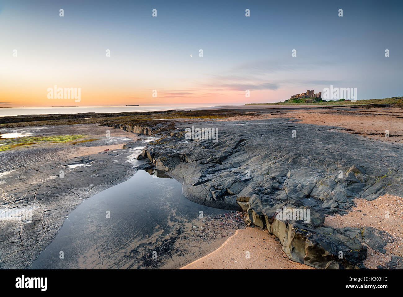 Low tide on the beach at Bamburgh Castle on the Northumberland coast - Stock Image