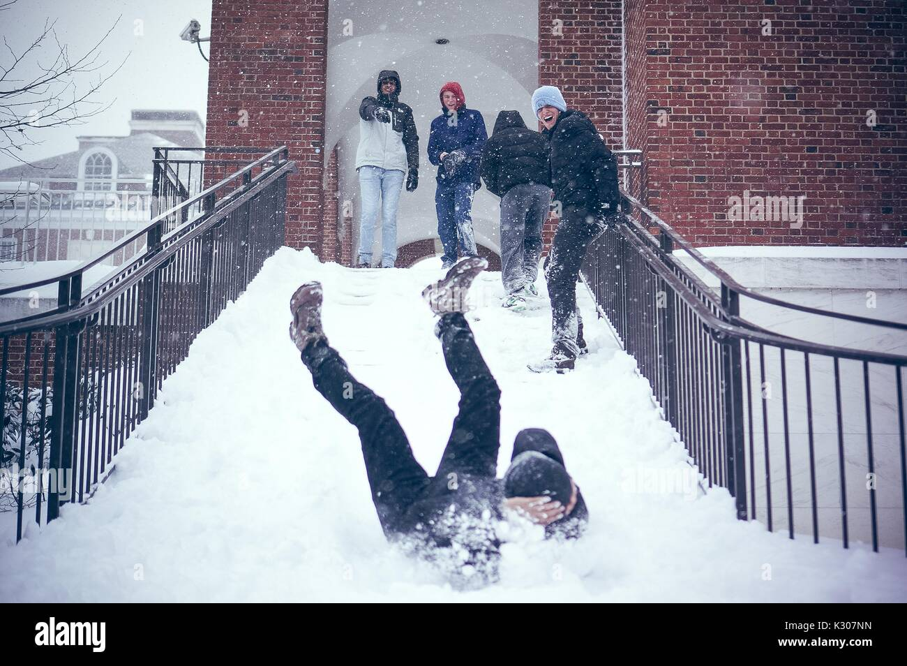 A student slides down a snowy staircases with legs in the air and arms covering his head, while other students in snow gear smile and cheer at the top of the stairs, on a snow day at Johns Hopkins University, Baltimore, Maryland, 2016. - Stock Image