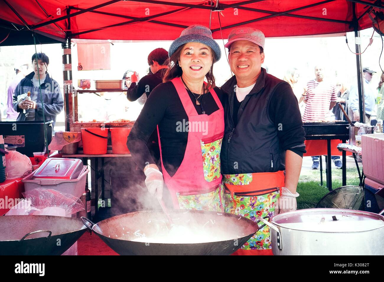 A man and woman wearing hats and aprons smile next to each other for a photo behind three large woks and pots, while the woman stirs the noodles in the wok with a gloved hand, at a food booth during Spring Fair, a student-run spring carnival at Johns Hopkins University, Baltimore, Maryland, April, 2016. Courtesy Eric Chen. - Stock Image