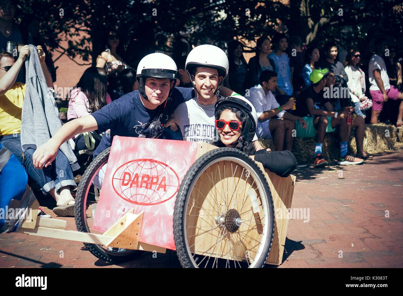 Three students wearing helmets pose for a photo from inside a wooden cart with wheels, as onlookers watch from the side in the shade, during a carnival game at Spring Fair, a student-run spring carnival at Johns Hopkins University, Baltimore, Maryland, April, 2016. Courtesy Eric Chen. - Stock Image