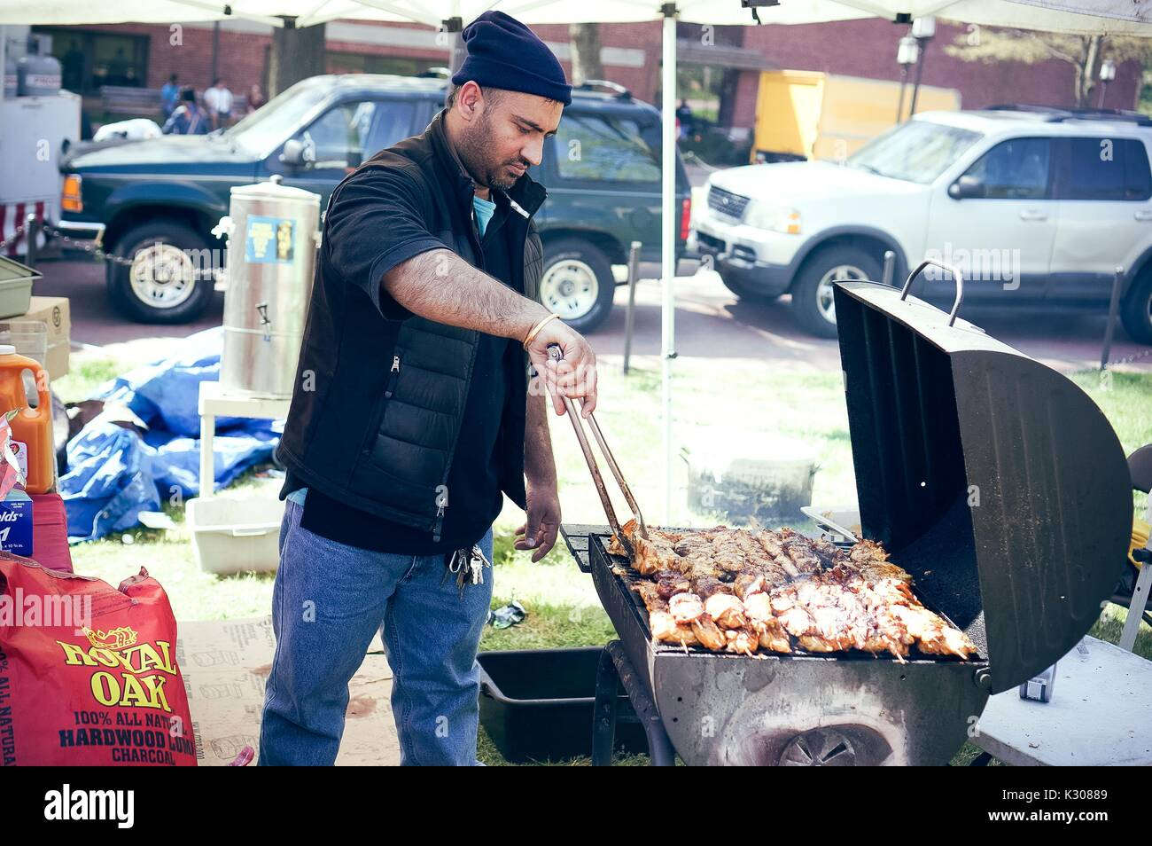 A man wearing beanie and vest stands in front of a grill, cooking chicken on skewers using large tongs, at a food booth during Spring Fair, a student-run spring carnival at Johns Hopkins University, Baltimore, Maryland, April, 2016. Courtesy Eric Chen. - Stock Image