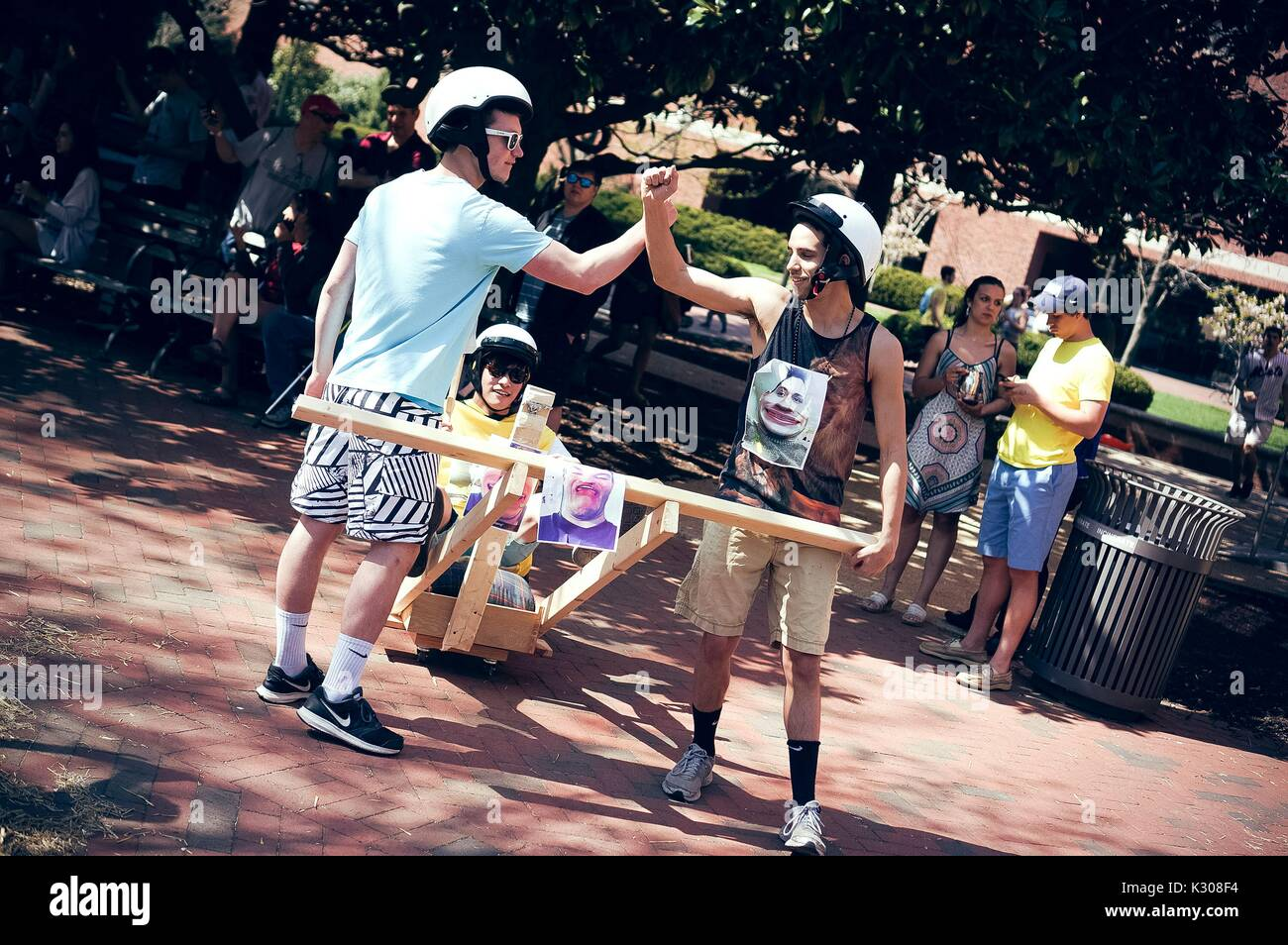 Two male students wearing white helmets throw up their hands to high-five while their teammate sits in a wooden contraption, onlookers watching from the shade, during a carnival game at Spring Fair, a student-run spring carnival at Johns Hopkins University, Baltimore, Maryland, April, 2016. Courtesy Eric Chen. - Stock Image