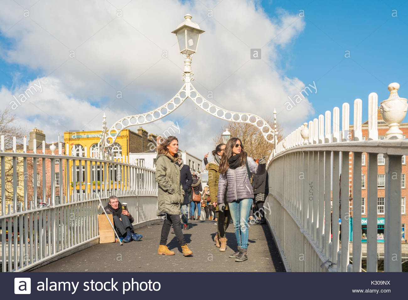 begging in Dublin - beggar and tourists on Ha'penny Bridge, Dublin, Ireland - Stock Image