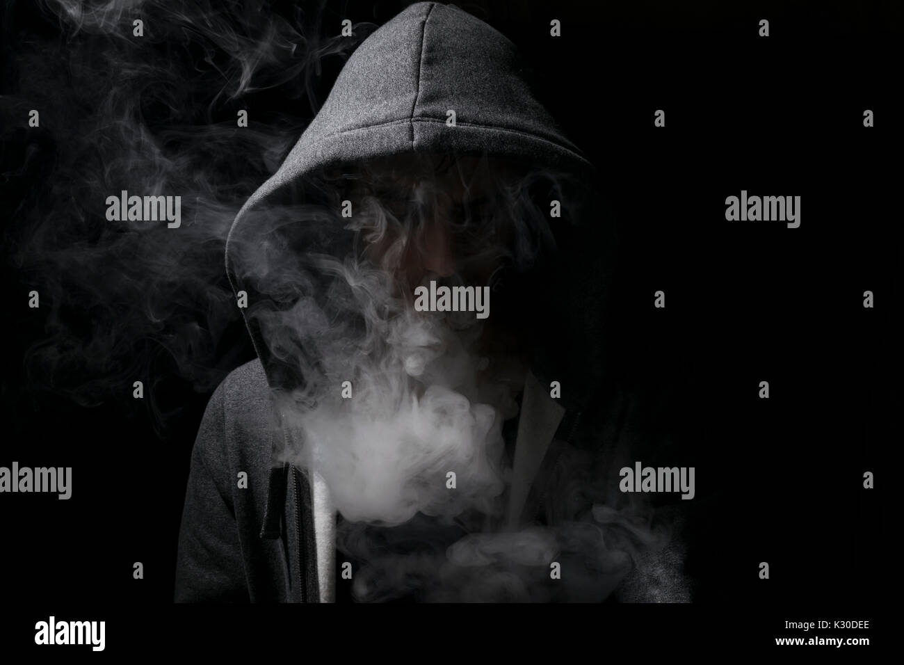 vaping man wearing a hoody with lots of smoking clouds. - Stock Image