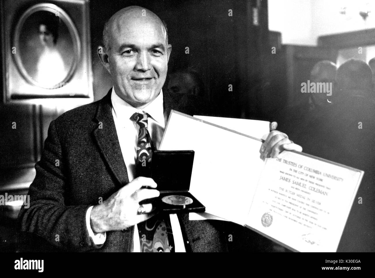 Sociological theorist and professor at Johns Hopkins University James Samuel Coleman holding up a medal and certificate, 1965. - Stock Image