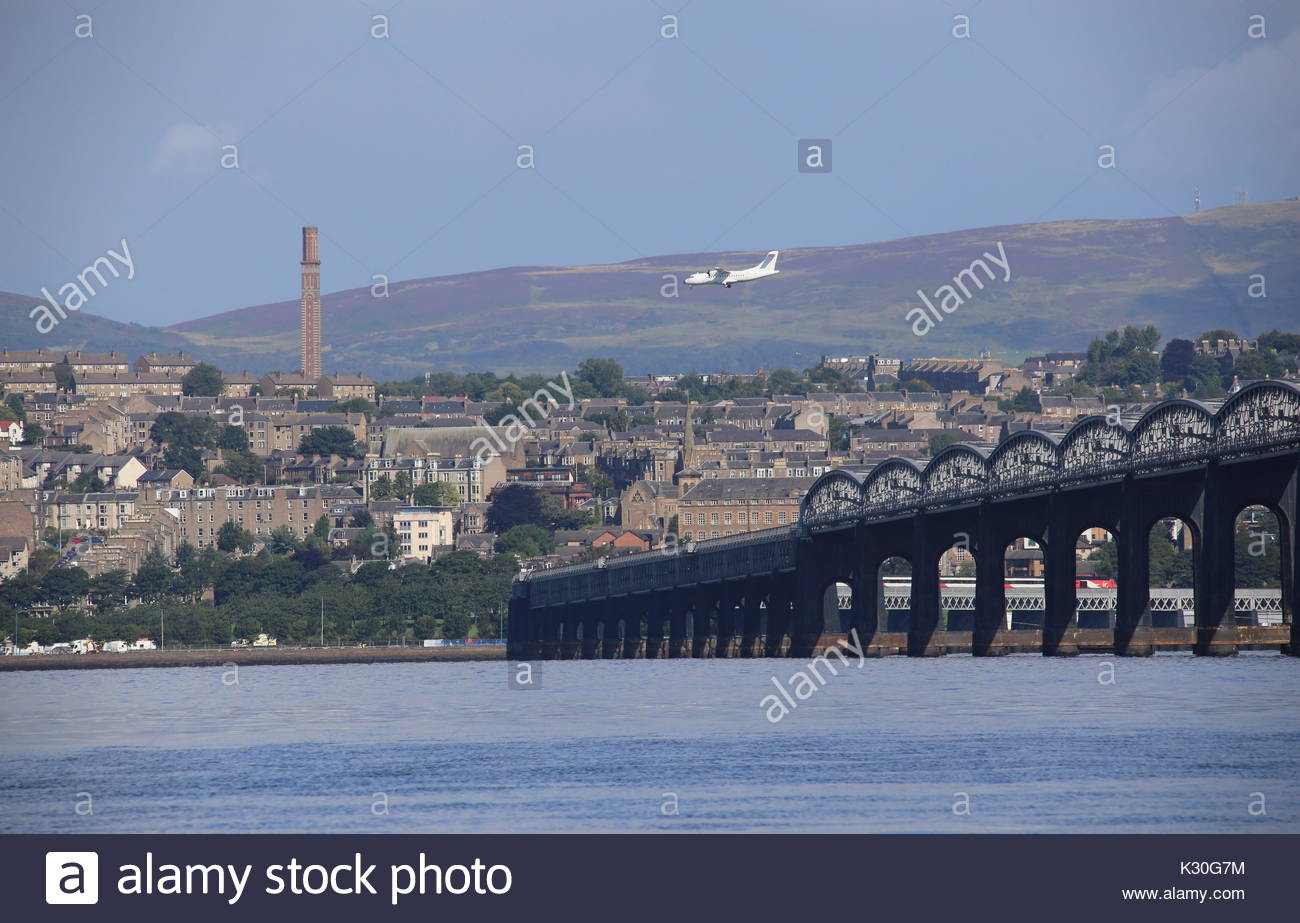 Plane on final approach to Dundee airport with Tay Rail Bridge and Cox's Stack chimney Scotland  August 2017 - Stock Image
