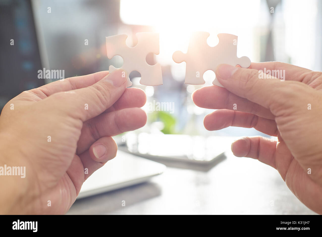 Young businessman trying to connect couple puzzle piece with sun flare and blur background,symbol of association and connection. business strategy. - Stock Image