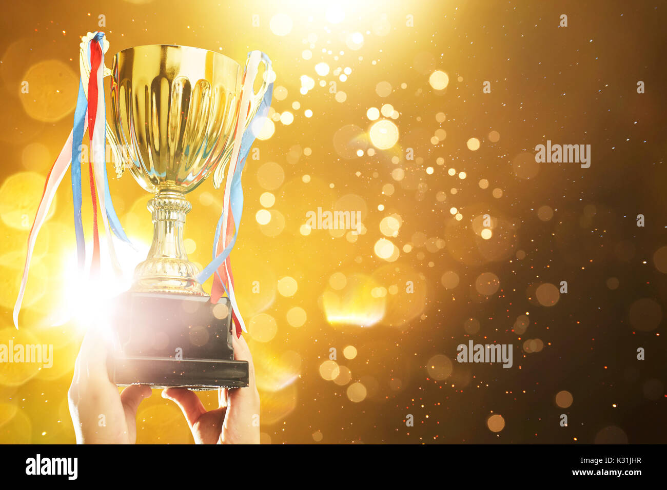 Hand raised, holding gold cup with abstract shiny lights . award and victory concept . - Stock Image