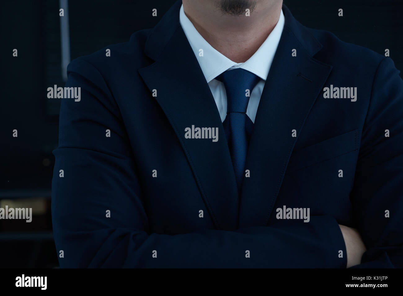 Part of man body side folded his arms in black suit on black background, business concept . - Stock Image