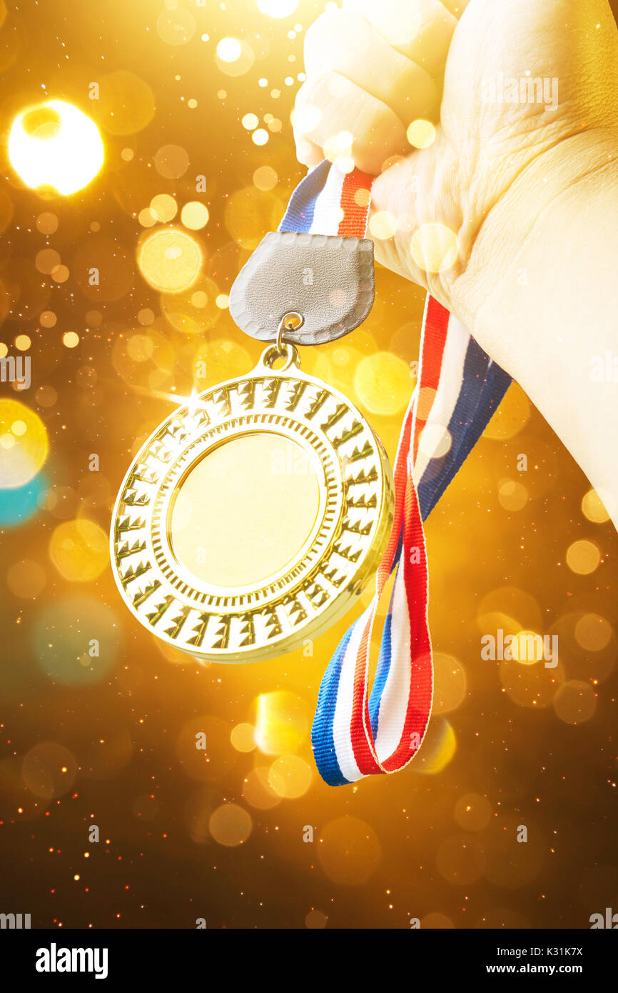 Hand raised, holding gold medal with abstract shiny lights . award and victory concept . - Stock Image
