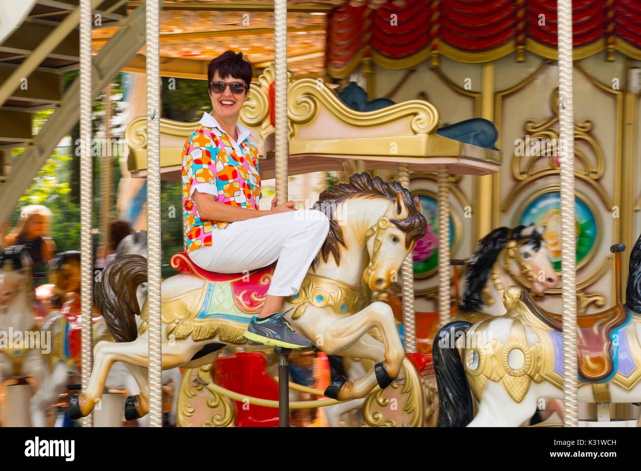 Woman riding traditional gallopers on a carousel ride, Santander. Cantabria Spain, Europe - Stock Image