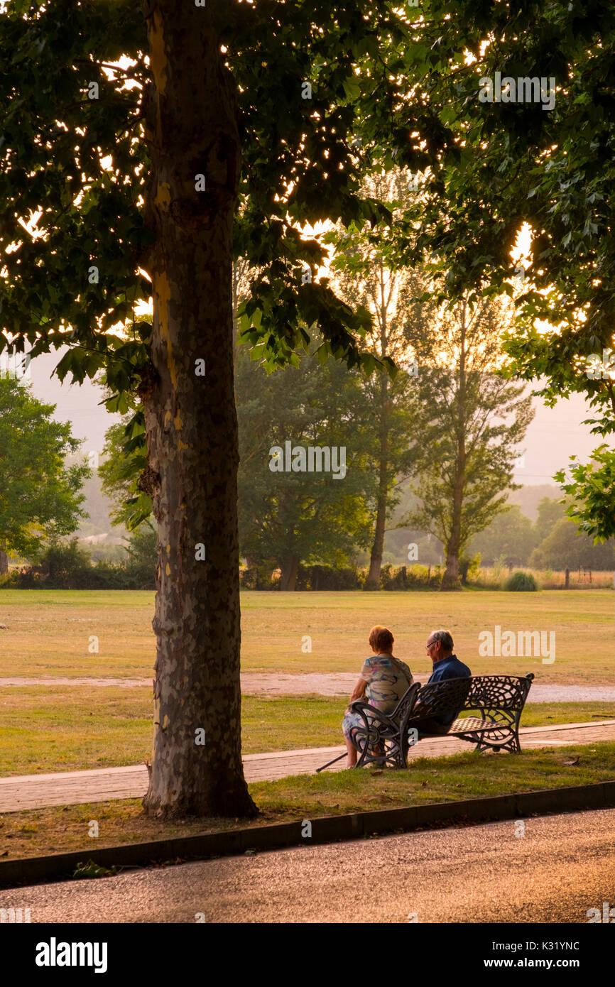 Elderly couple sitting on a bench at sunset in the park. Villarcayo. Burgos province, Castilla-León, Spain Europe Stock Photo