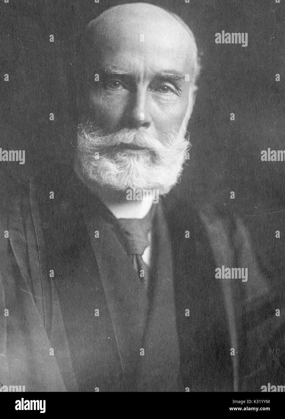 Sepia tone portrait, shoulders up, of Samuel Fessenden Clarke, famed zoologist, professor of natural history, and fellow at Johns Hopkins University, with beard and wearing academic robe and tie, Baltimore, Maryland, 1920. - Stock Image