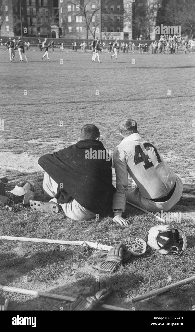 Sepia tone candid photograph of two co-captains of the men's lacrosse team at Johns Hopkins University, Joe Sollers and Byron Forbush, sitting from the sideline on the grass with backs turned, watching the end of the match, with lacrosse sticks and gloves scattered behind them, Baltimore, Maryland, June, 1951. - Stock Image
