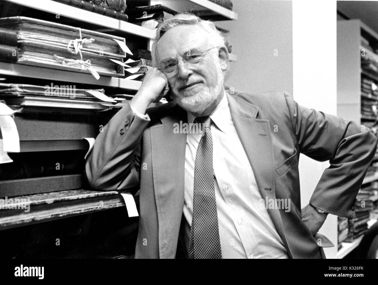 Jerome Melvin Edelstein, bibliographer and scholar within many fields of the humanities, leans against shelves holding materials from a library's special collections, 1990. - Stock Image