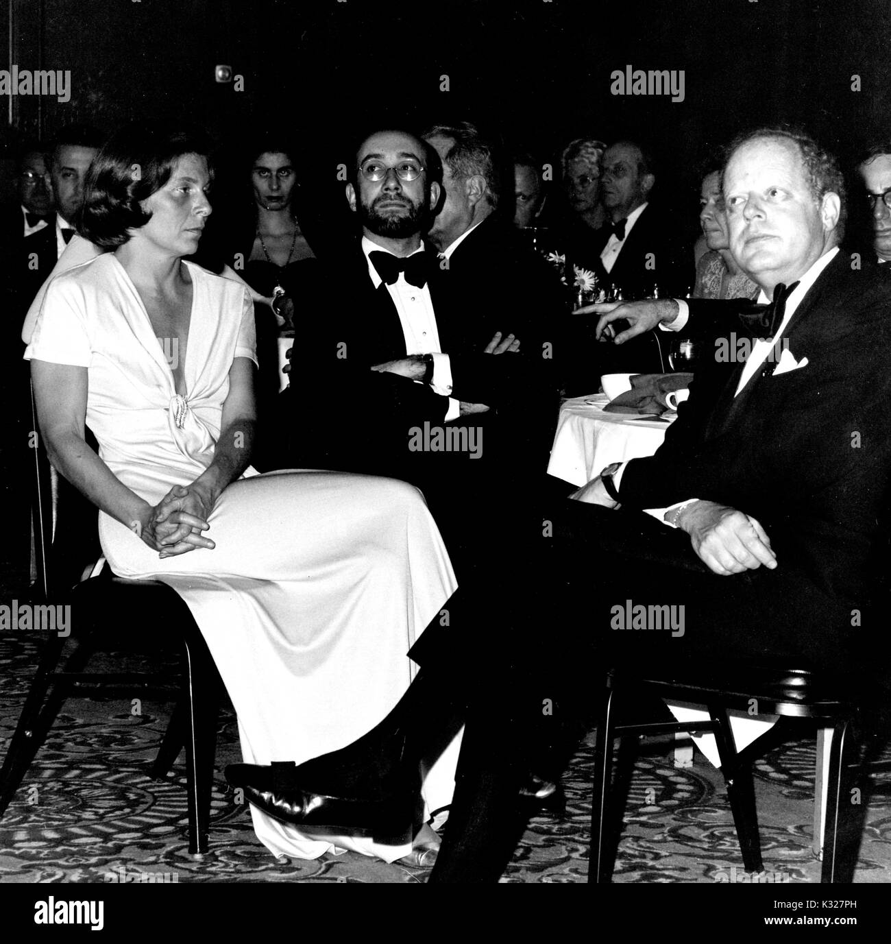 Political, social, and civic figure Eleanor Hutzler (left), her husband and chairman of Hutzler Brothers department store chain Charles Hutzler (center), and art historian and museum director Tom Freudenheim (right) sit around a table during Johns Hopkins University's Centennial Dinner, February 21, 1976. - Stock Image