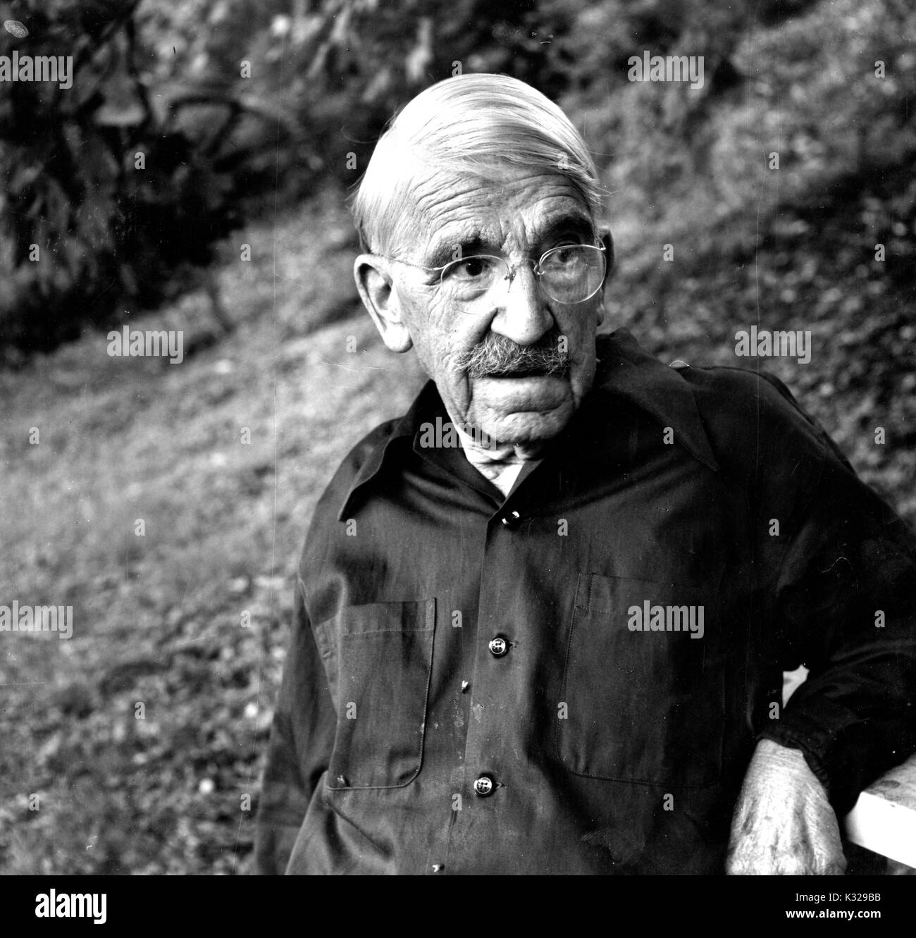 Candid portrait of American philosopher, psychologist, and educational reformer John Dewey standing in a wooded area, 1935. - Stock Image