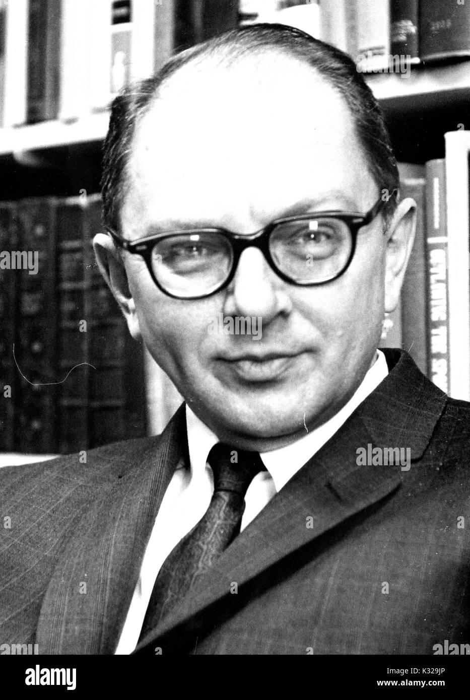 Portrait photograph of American historian and biographer David Herbert Donald sitting in front of bookshelves, 1962. - Stock Image