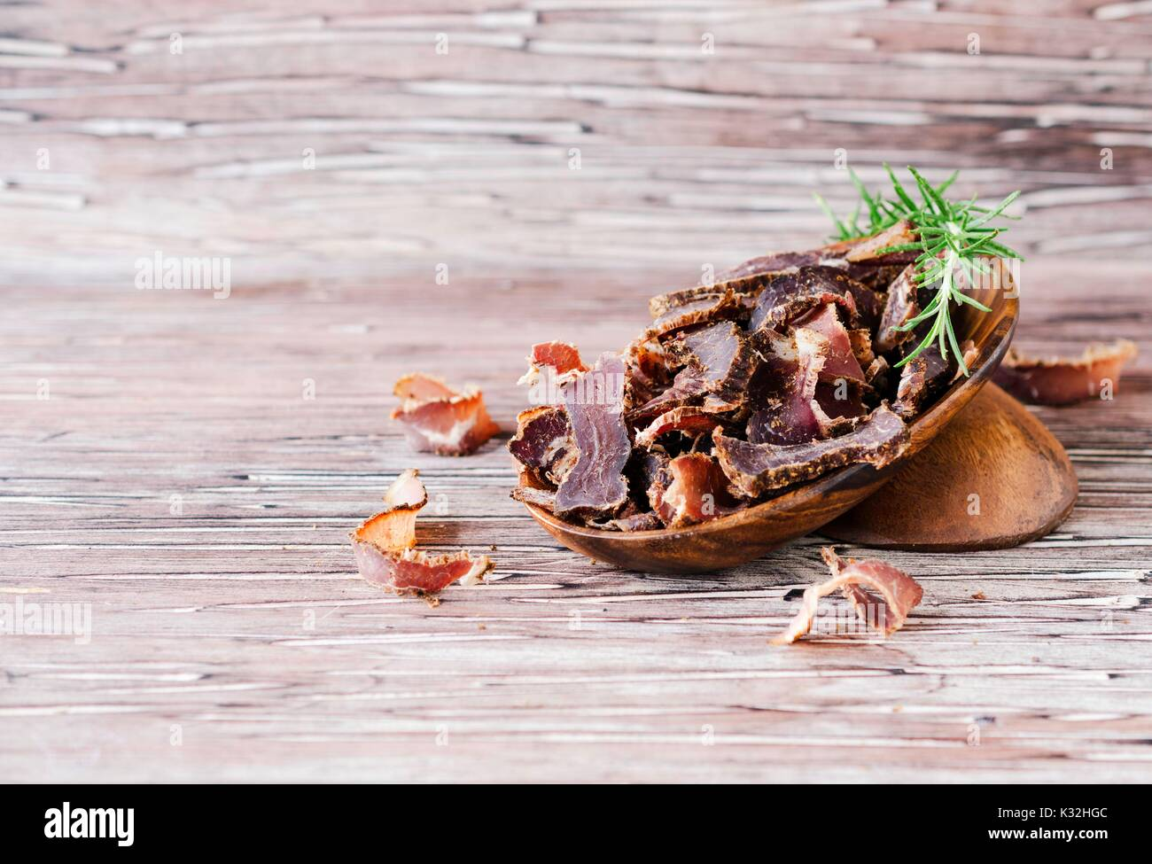 jerked meat, cow, deer, wild beast or biltong in wooden bowls on a rustic table, selective focus - Stock Image