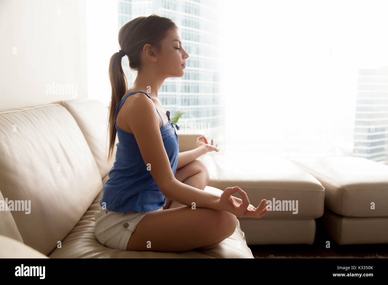 Lady practicing yoga and relaxing at home - Stock Image