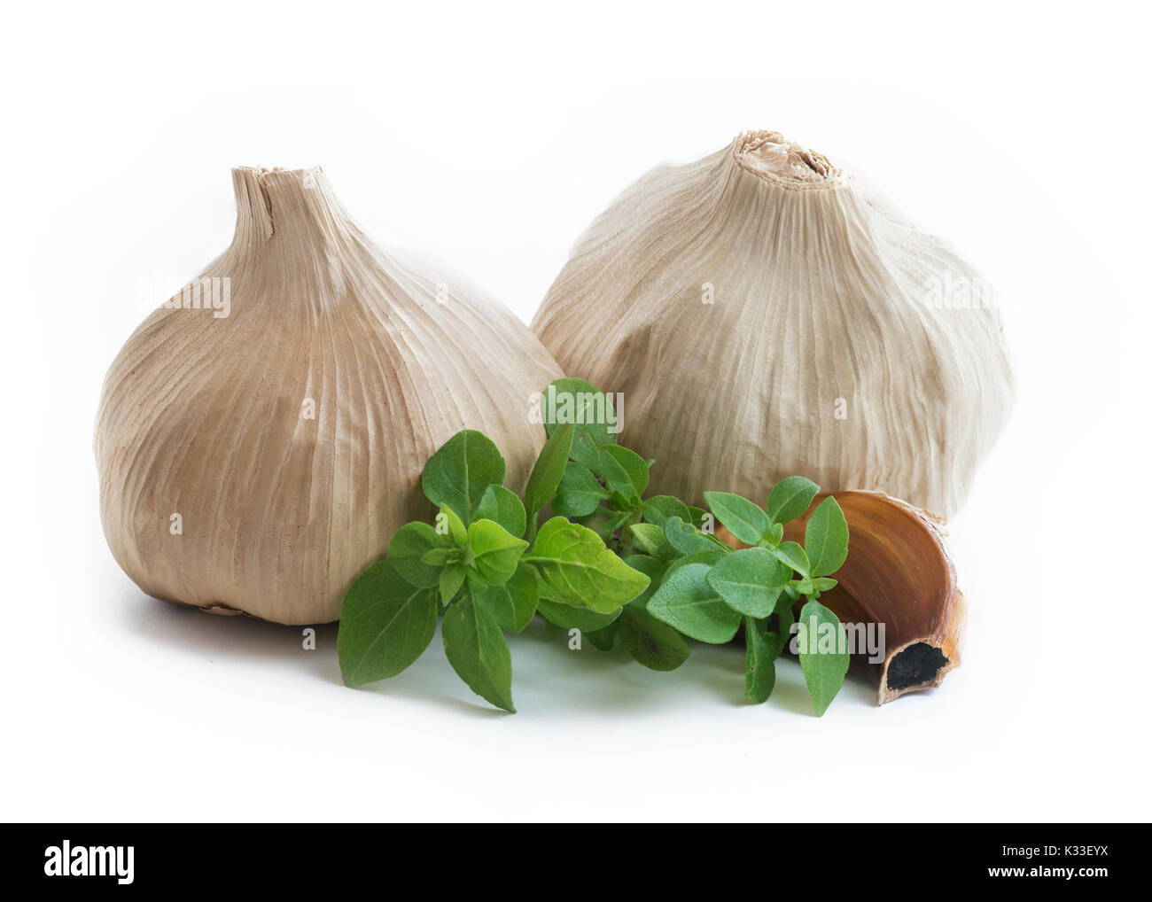 Whole bulb of home fermented  Black Garlic with cloves, latest wonder food ,rich in antioxidants, vitamins and minerals. Isolated on white background  - Stock Image