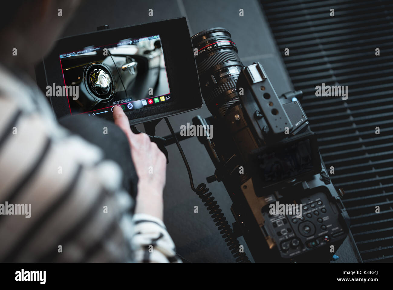 Hand of the camera operator touching a modern DSLR - Stock Image