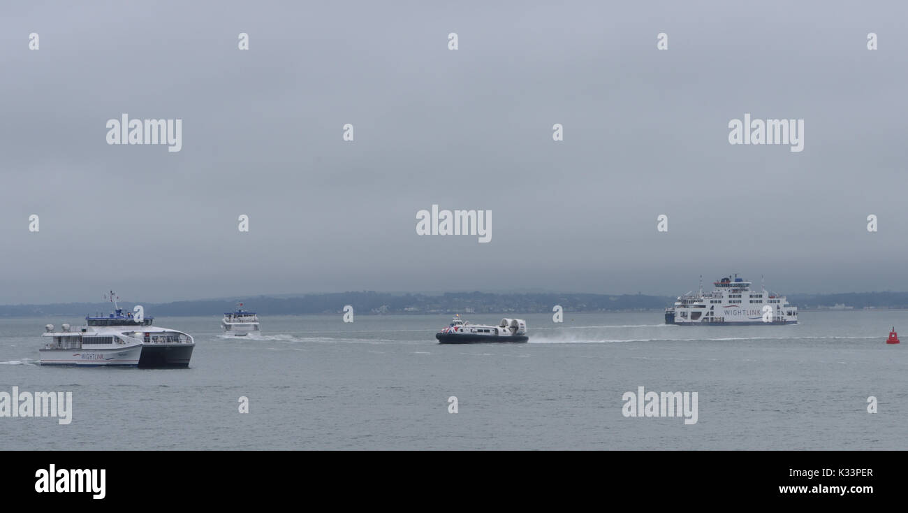 On a dull, grey, cloudy day a variety of ferries cross the Solent between different parts of Portsmouth and the Isle of Wight: Wightlink, hovercraft, - Stock Image