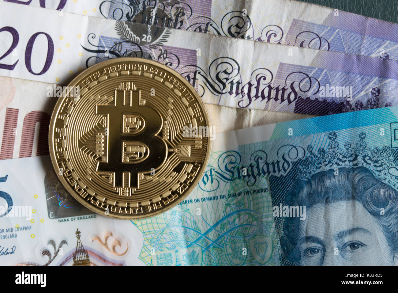 A bitcoin on top of GB Sterling notes - Stock Image