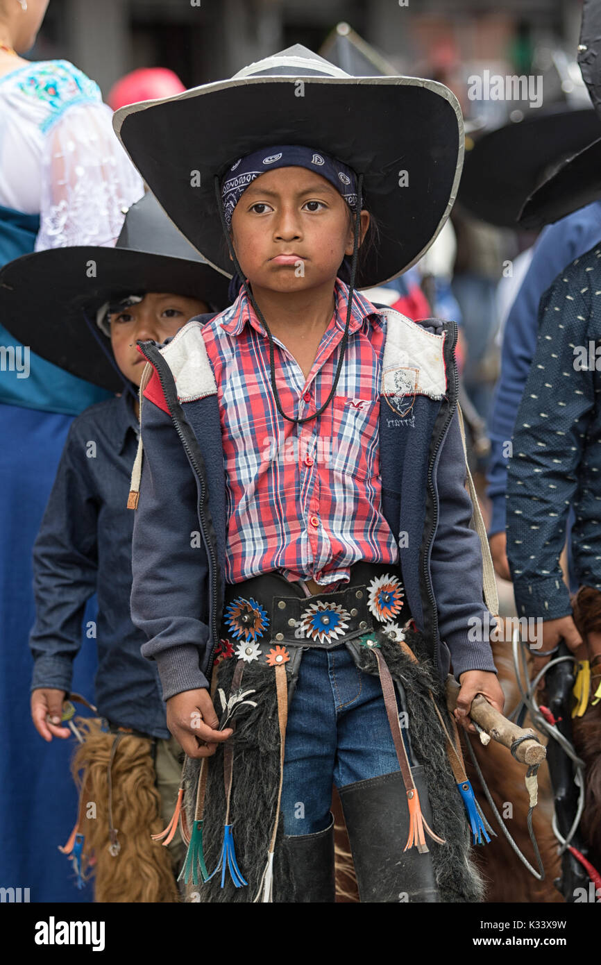 June 24, 2017 Cotacachi, Ecuador: indigenous quechua children wearing chaps and sombreros participating at the Inti Raymi parade - Stock Image