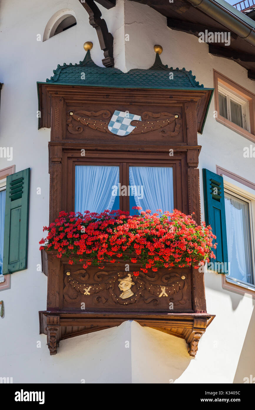 Red flowers and wood decorate the windows of the typical houses Garmisch Partenkirchen Oberbayern region Bavaria Germany Europe - Stock Image