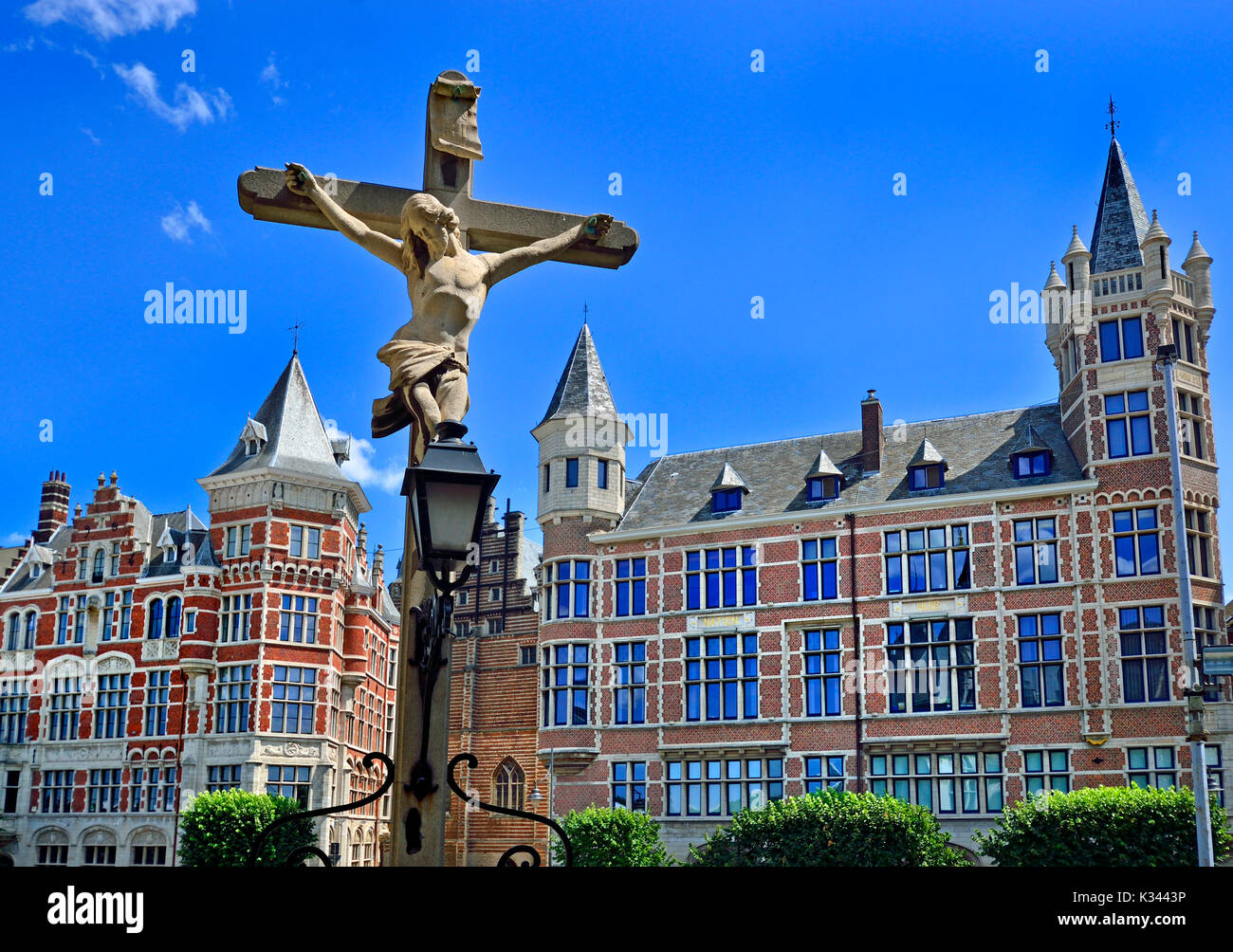 Antwerp, Belgium. View from Het steen - medieval fortress by the river. Stone Crucifix and buildings on Jordaenskaai - Stock Image