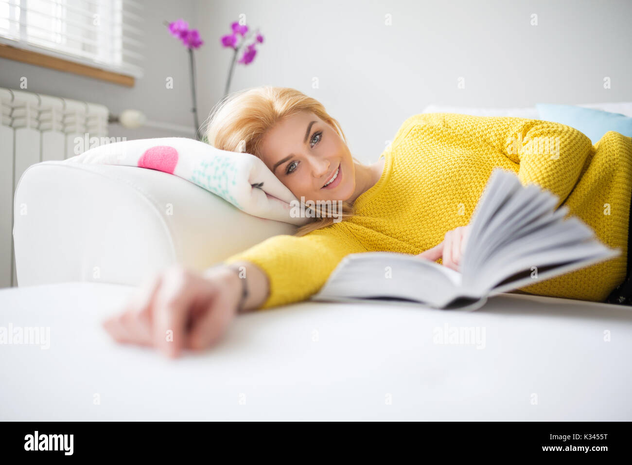 A photo of young, beautiful woman lying on the couch and reading book. She's smiling happily. - Stock Image