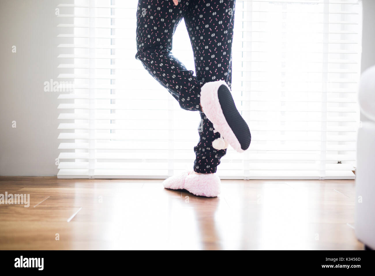 A photo of person in pajamas trousers standing on one foot. - Stock Image