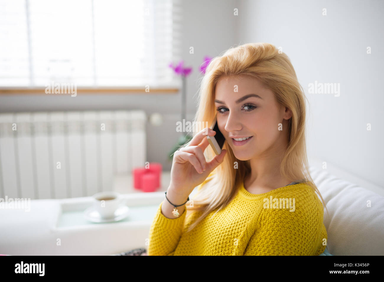 A photo of young, beautiful woman sitting on the couch and talking on the phone. - Stock Image