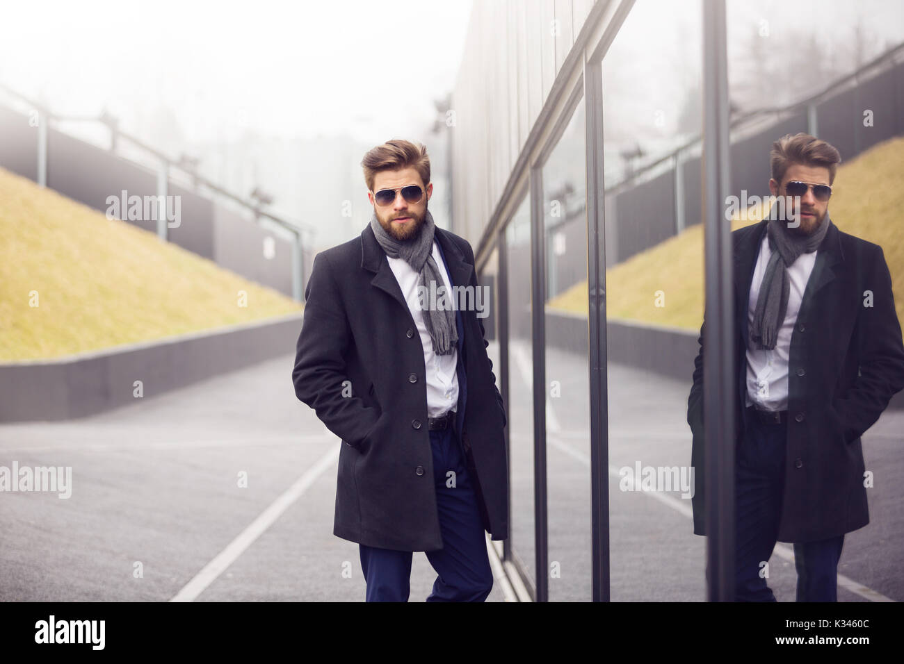 A photo of young, fashionable buinessman standing next to modern building and posing to the photo. - Stock Image