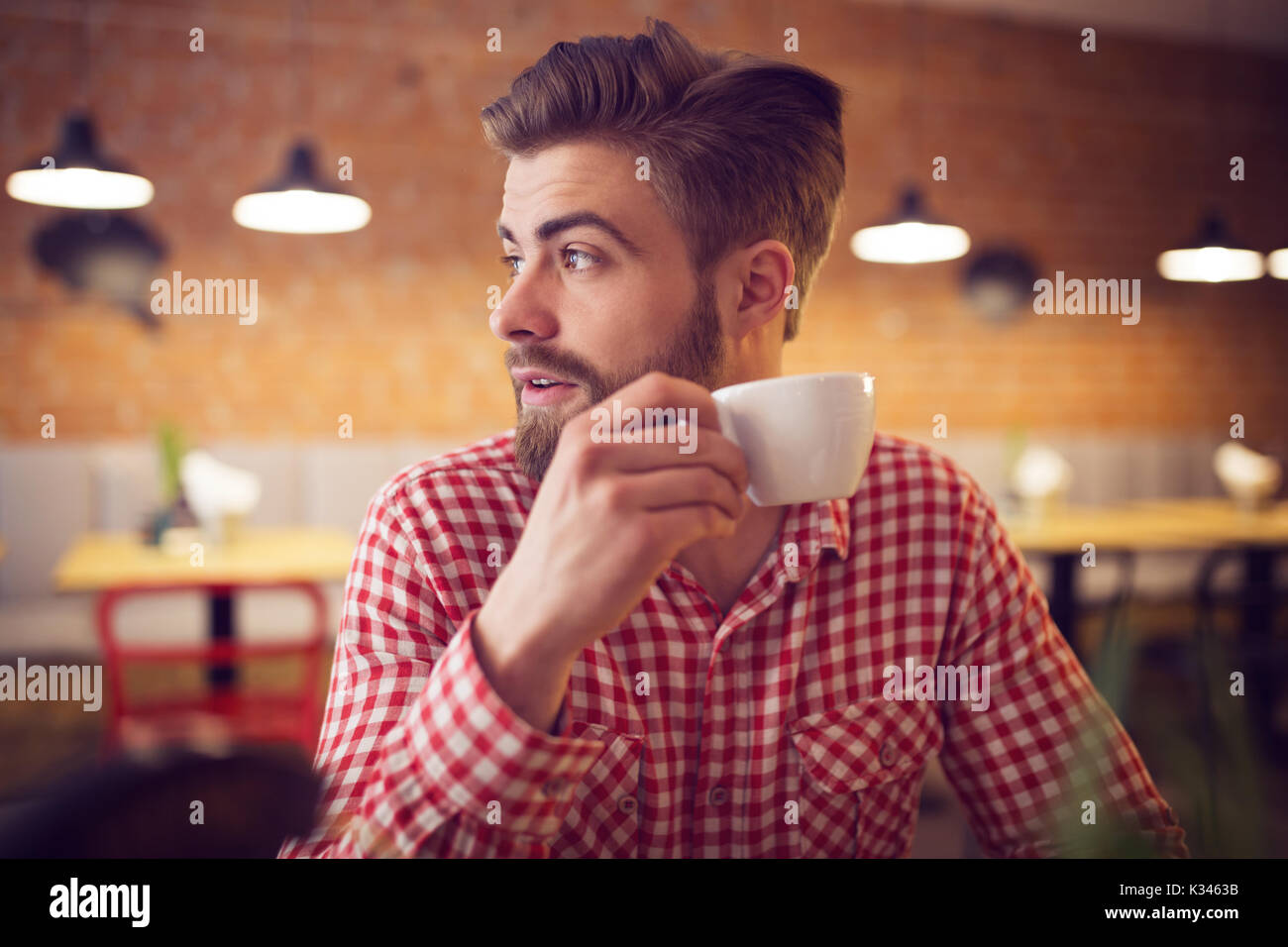 A photo of young man in checked shirt sitting at the cafe with a cup of coffee in his hand. - Stock Image