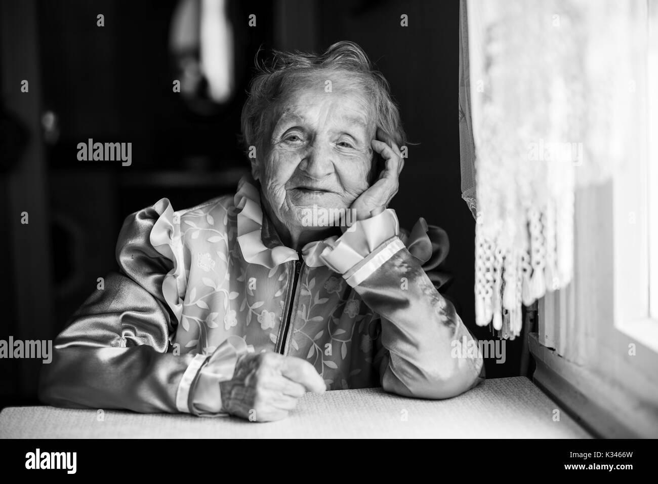 Slavic ethnic portrait of an elderly woman. Black and white photo. - Stock Image
