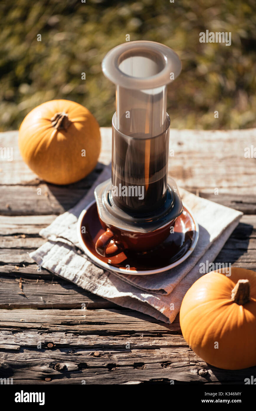 Autumn outdoor coffee picnic. Coffee cups, cute little pumpkin on the old table background - Stock Image