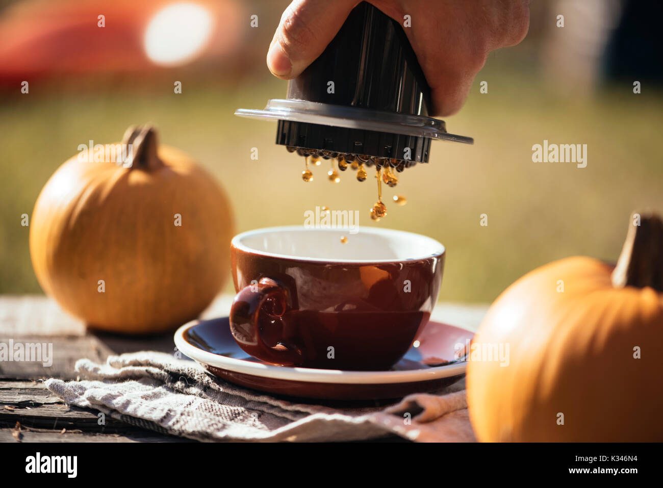 Man brewing filter coffee outdoor, at the autumn coffee picnic, on the old damaged wooden table background. Coffee drips captured in motion in the pro - Stock Image