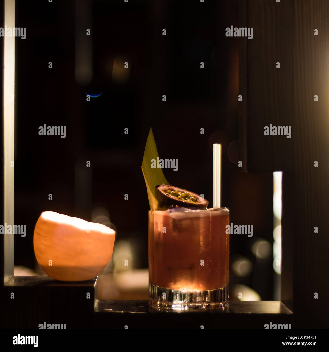 Fruit cocktail lit by candle and garnished with fig and leaf. Alcoholic drink in old fashioned glass in bar - Stock Image